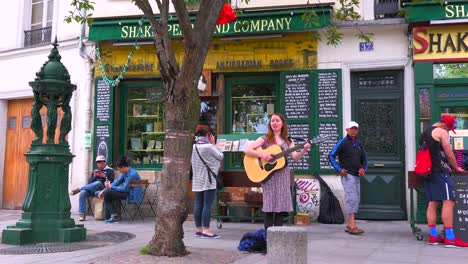 A-girl-plays-folk-music-outside-a-bookstore-and-cafe-in-Paris