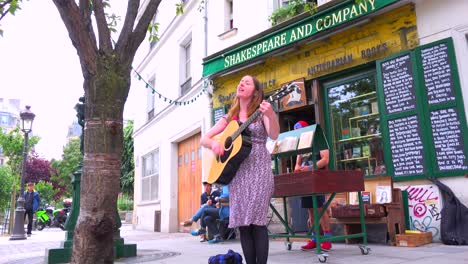 A-girl-plays-folk-music-outside-a-bookstore-and-cafe-in-Paris-1