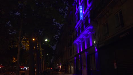 A-neon-sign-identifies-a-European-hotel-at-night