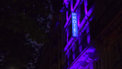 A-neon-sign-identifies-a-European-hotel-at-night-1