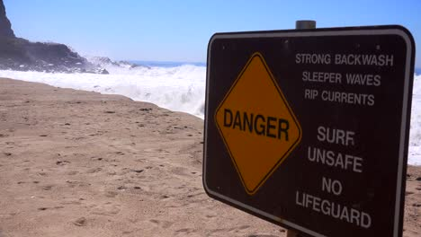 A-sign-along-a-California-beach-warns-of-dangerous-surf-and-strong-rip-currents