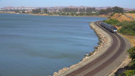 An-Amtrak-train-passes-along-a-shoreline-in-the-Bay-Area-of-California