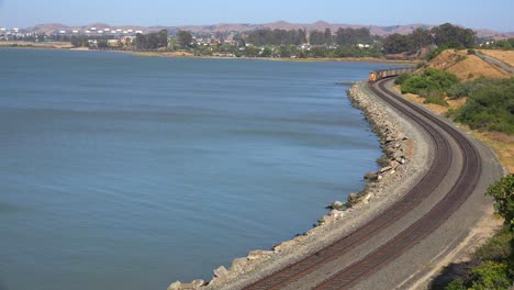 A-fast-moving-freight-train-passes-along-a-shoreline-in-the-Bay-Area-of-California