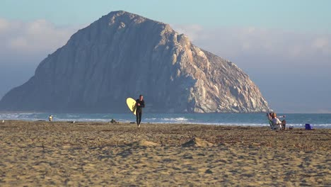 A-surfer-crosses-in-front-of-the-beautiful-Morro-Bay-rock-along-California-s-central-coast