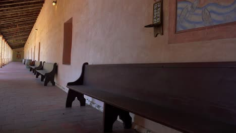 Wooden-benches-line-the-adobe-walls-of-a-California-Mission