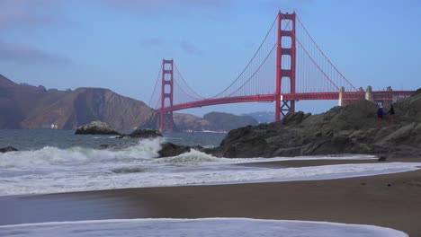 A-view-across-Baker-Beach-in-San-Francisco-to-the-Golden-Gate-Bridge-with-waves-crashing-on-shore