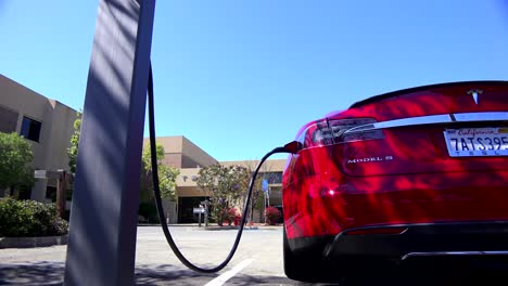 Traveling-shot-along-the-back-of-a-Tesla-electric-car-as-it-charges