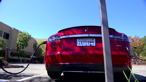 Traveling-shot-along-the-back-of-a-Tesla-electric-car-as-it-charges-1