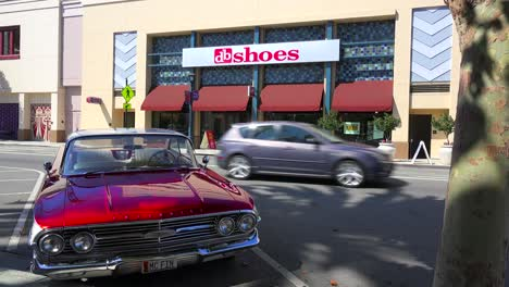 Exterior-establishing-shot-of-a-shoe-store-with-a-classic-car-foreground