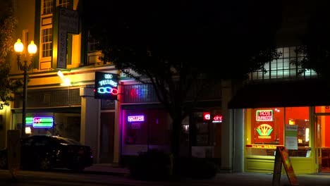 Establishing-shot-of-a-small-retail-storefront-business-district-at-night