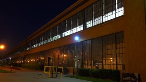 An-establishing-shot-of-a-warehouse-or-factory-at-night