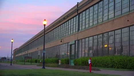 An-establishing-shot-of-a-warehouse-or-factory-at-sunset