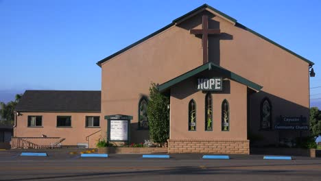 An-old-brown-church-displays-a-cross-and-says-hope