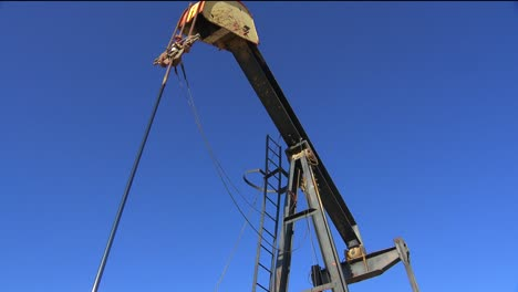 Low-angle-view-in-an-oilfield-of-an-oil-derrick-pumping