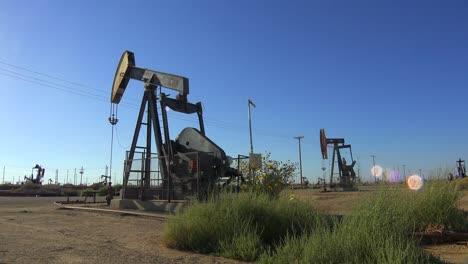 Establishing-shot-of-an-oil-field-with-derricks-pumping