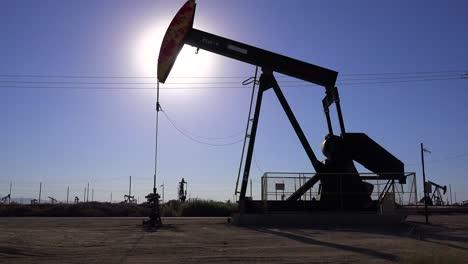 Establishing-shot-of-an-oil-field-with-derricks-pumping-against-the-sun