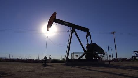 Eröffnungsaufnahme-Eines-Ölfeldes-Mit-Bohrtürmen-Die-Gegen-Die-Sonne-Pumpen-1