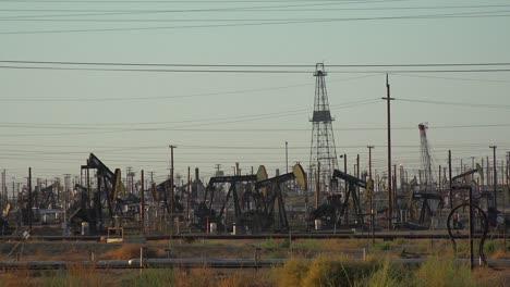Wide-shot-of-many-oil-derricks-pumping-in-a-vast-oilfield