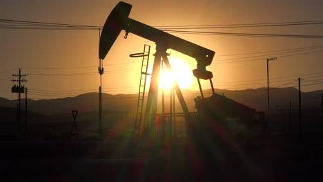 An-oil-derrick-pumps-against-a-sunset-sky