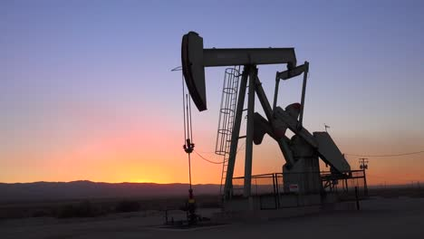 An-oil-derrick-pumps-against-the-horizon-at-dusk