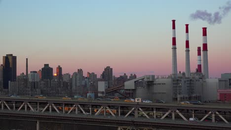 Dusk-view-across-Queens-to-upper-Manhattan-in-new-York-City-with-power-plant-smokestacks-and-Queensboro-Bridge