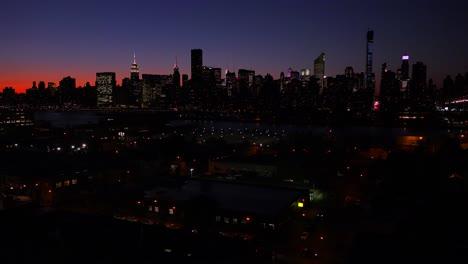 Una-Vista-De-Gran-Angular-Sobre-La-Ciudad-De-Nueva-York-Queens-Al-Anochecer-Con-El-Fondo-Del-Horizonte-De-Manhattan