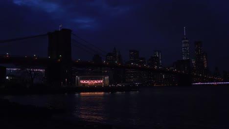 Die-Skyline-Von-New-York-City-Mit-Der-Brooklyn-Bridge-Im-Vordergrund-Bei-Nacht