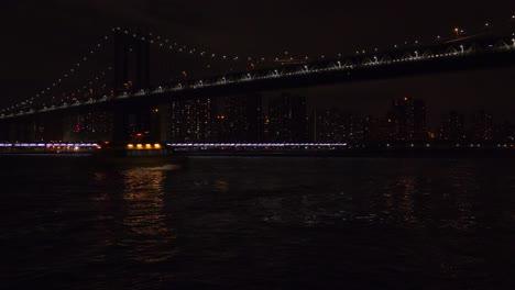 Die-Brooklyn-Bridge-Bei-Nacht-Mit-Der-Skyline-Von-New-York-City-Im-Hintergrund-Und-Der-U-Bahn-Vorbei