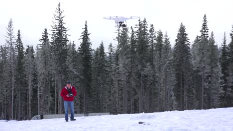 A-man-flies-a-commercial-drone-quadcopter-on-a-snowy-day-1