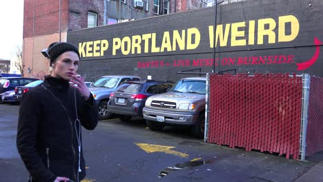 A-man-stands-in-front-of-a-sign-on-a-building-urging-visitors-to-keep-Portland-weird
