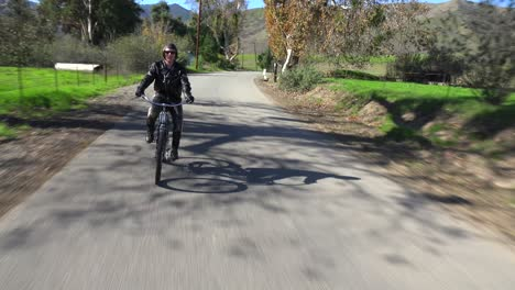A-man-in-leather-jacket-drives-a-motorized-bicycle-along-a-country-road