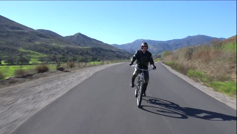 A-man-in-leather-jacket-drives-a-motorized-bicycle-along-a-country-road-1