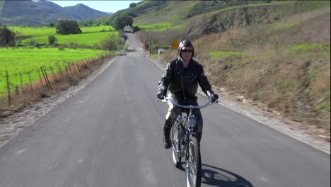 A-man-in-leather-jacket-drives-a-motorized-bicycle-along-a-country-road-2