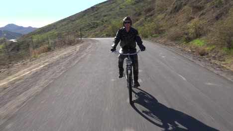 A-man-rides-a-motorized-bicycle-through-the-countryside-on-a-two-lane-road