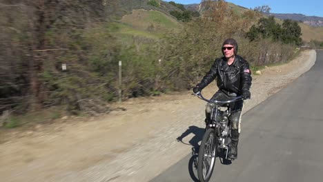 A-man-in-leather-jacket-drives-a-motorized-bicycle-along-a-country-road-3