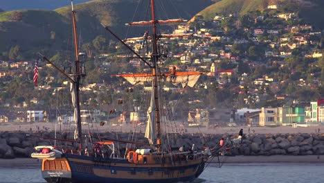 A-tall-clipper-ship-sails-at-sunset-with-the-city-of-Ventura-California-in-the-distance