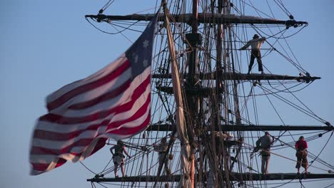 Sailors-stand-on-the-mast-of-a-tall-historic-clipper-ship-as-it-sails-on-the-ocean