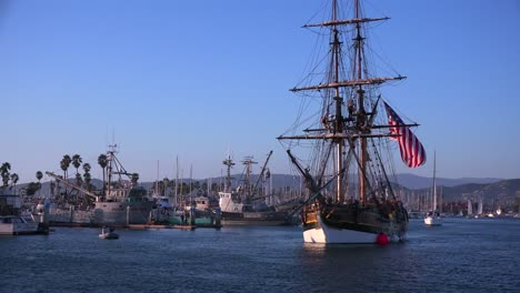 Sailors-stand-on-the-mast-of-a-tall-historic-clipper-ship-as-it-sails-in-the-harbor-in-Ventura-California