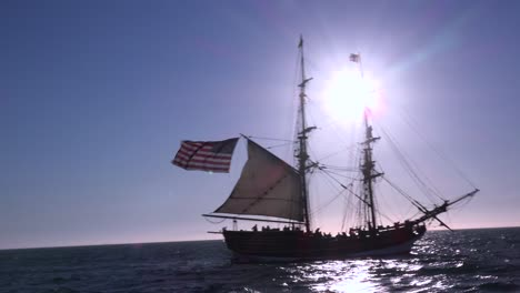 A-tall-masted-clipper-ship-sails-on-the-high-seas-with-an-american-flag-flying
