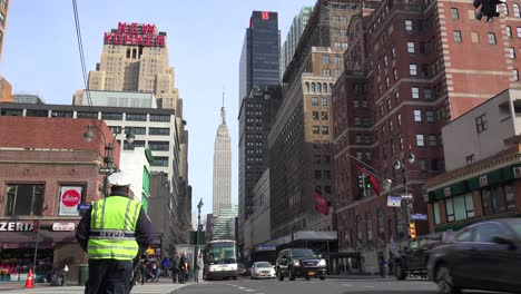 A-New-York-City-policeman-directs-traffic-with-the-Empire-State-building-in-the-background-1