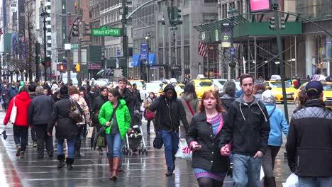 La-Gente-Camina-Por-Una-Calle-En-El-Centro-De-Manhattan-Bajo-La-Lluvia-Con-El-Tráfico-Que-Pasa