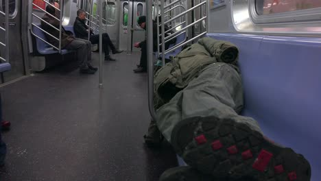 A-homeless-man-sleeps-in-a-subway-train
