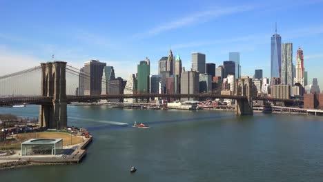 Schöne-Aufnahme-Des-Finanzviertels-Von-New-York-City-Mit-Brooklyn-Bridge-Vordergrund-Und-Booten-Die-Unterfahren-