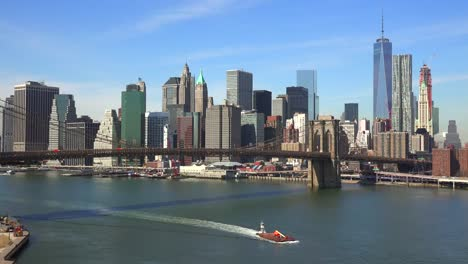 Schöne-Aufnahme-Des-Finanzviertels-Von-New-York-City-Mit-Brooklyn-Bridge-Vordergrund-Und-Booten-Unter-1-Passing
