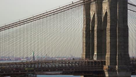 Ein-Blick-Durch-Die-Brooklyn-Bridge-Mit-Der-Freiheitsstatue-In-Der-Ferne