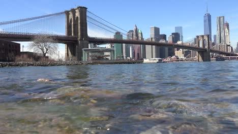 Wasserstandsaufnahme-Des-New-Yorker-Finanzviertels-Mit-Brooklyn-Bridge-Vordergrund-Und-Booten-Die-Unterfahren