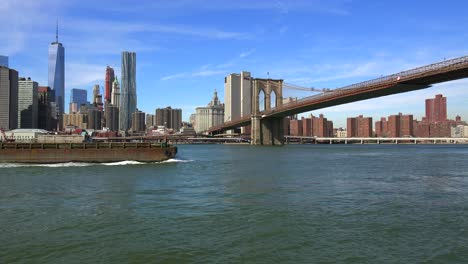 A-barge-and-tugboat-moves-up-New-York-s-East-River-and-crosses-under-the-Brooklyn-Bridge