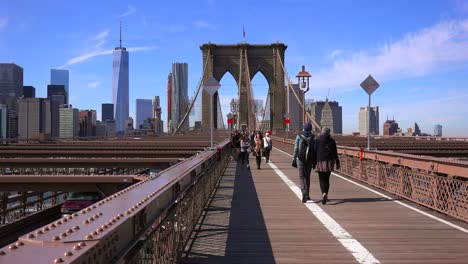 Pedestrians-cross-the-Brooklyn-Bridge-with-Manhattan-and-the-Freedom-Tower-in-the-distance