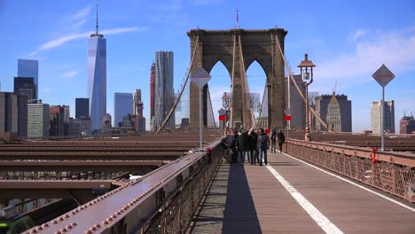 Pedestrians-cross-the-Brooklyn-Bridge-with-Manhattan-and-the-Freedom-Tower-in-the-distance-1