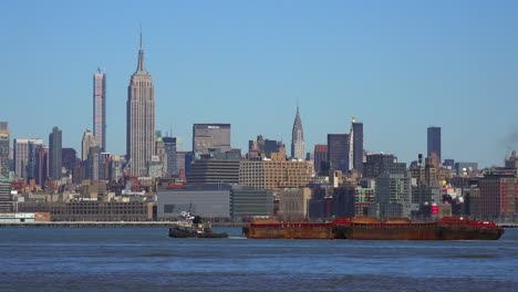 A-tugboat-pulls-a-barge-on-the-Hudson-River-in-New-York-City-with-the-Empire-State-Building-background